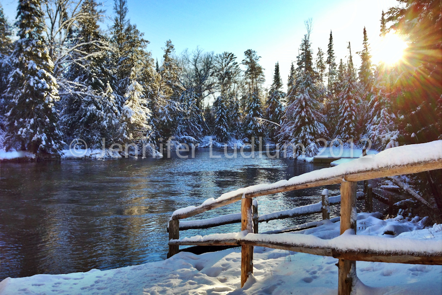 Au Sable River with sun glimmering above the snow covered trees.