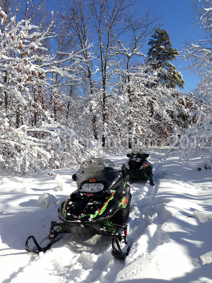 Snowmobiles parked on trail
